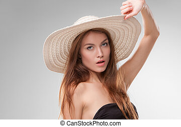 Beautiful girl with hat posing in studio