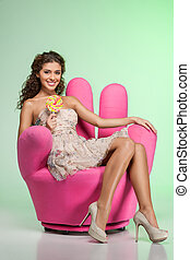 Beautiful girl with lollipop. Attractive young women holding a lollipop while sitting on funky chair isolated on green