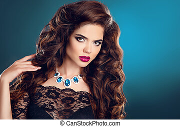 Beautiful girl with long curly hair and red lips makeup, gems expensive necklace jewelry posing on dark blue studio background.