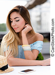 Beautiful girl with long hair. A woman in a summer cafe on the veranda of the restaurant. Sits at a table in blue dress, close-up. Resting after a hard day at the office