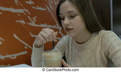 Beautiful girl with long hair drinks a drink in a cafe. Stir...