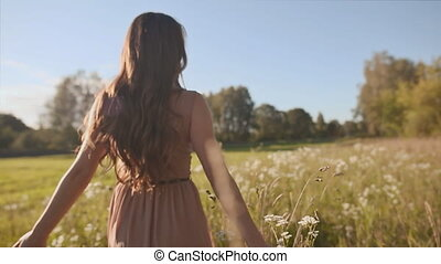 Beautiful girl with long hair goes in a green meadow, and touch the flowers.