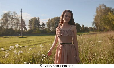 Beautiful girl with long hair goes in a green meadow, and touch the flowers. To whirl, to enjoy.
