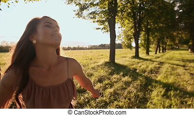 Beautiful girl with long hair goes on a green trail among the trees, circling and enjoying the sun and nature.