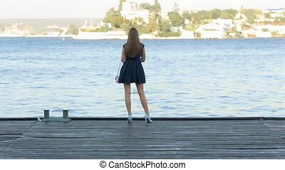 Beautiful girl with long hair in dress standing on a wooden pier and looking at the sea