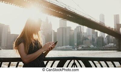 Beautiful girl with long hair in sunglasses using smartphone app at sunset river quay near Brooklyn Bridge New York 4K.