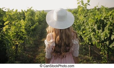 Beautiful girl with long hair in the hat walking through the vineyard