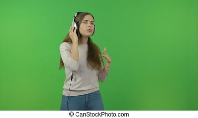 Beautiful girl with long hair listening to music through headphones. On the green screen. She dances and sings.