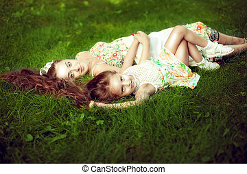 beautiful girl with long hair lying next to his pregnant mother in the summer on the green grass