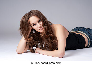 Beautiful girl with long hair lying on the floor