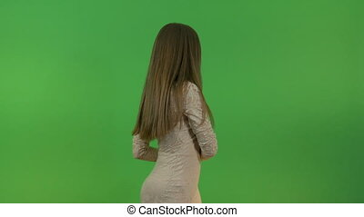 Beautiful girl with long hair makes a hand gesture in the studio on a green background.