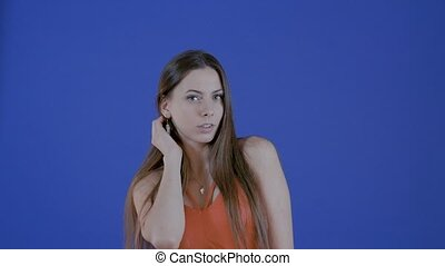 Beautiful girl with long hair posing for photo, in studio on blue background.