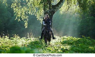 Beautiful girl with long hair rides a horse in the forest