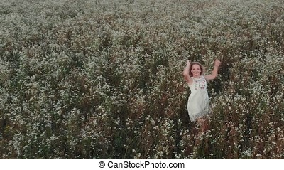 Beautiful girl with long hair running in a field with field flowers