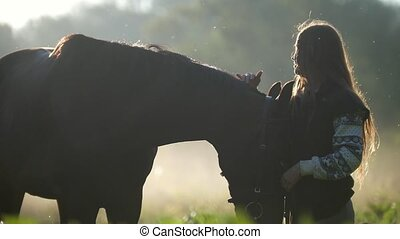 Beautiful girl with long hair stroking the horse in the rays...
