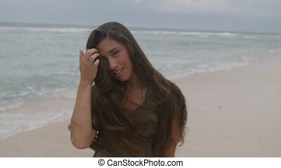 Beautiful girl with long hair walking along the shore of beach in Bali