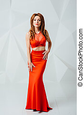 beautiful girl with long orange hair in red dress on white ...