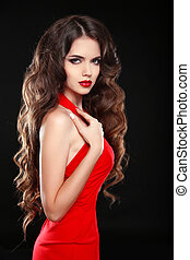 Beautiful girl with long wavy hair in red dress. Brunette with curly hairstyle posing isolaled on black background.