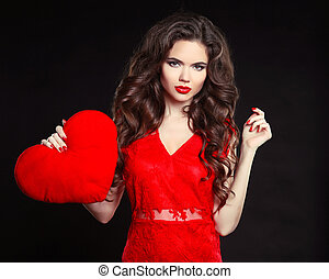 Beautiful girl with long wavy hair in red dress holding valentine's heart. Brunette with curly hairstyle and red lips isolated on black background.