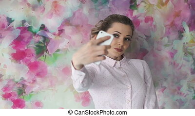 Beautiful girl with make-up making selfie on mobile phone in the studio