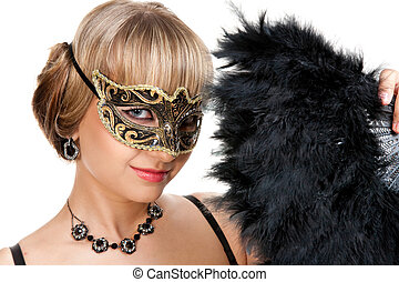 Beautiful girl with necklace and earrings in carnival mask hodling fan