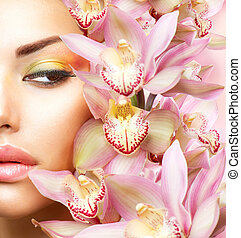 Beautiful Girl With Orchid Flowers. Beauty Model Woman Face