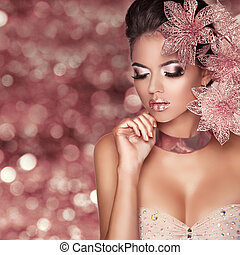 Beautiful Girl With Pink Flowers. Beauty Model Woman Face. Isolated on bokeh lights Background.  Perfect Skin. Professional Make-up. Makeup. Fashion Art.