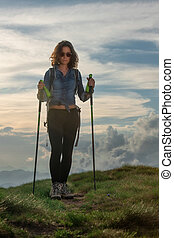 Beautiful girl with poles during a hike in the hills
