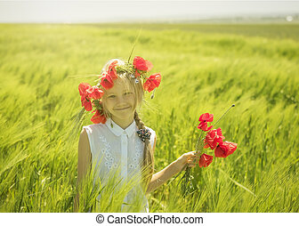 Beautiful girl with poppy flowers in the hands or on the head on a background of green rye.