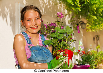 Beautiful girl with potted strawberries plants