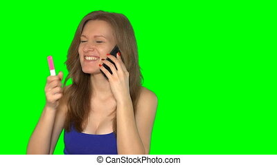Beautiful girl with pregnancy test talking on cell phone