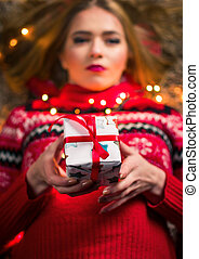 Beautiful girl with present box and festive lights