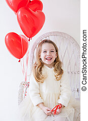 Beautiful girl with red balloons sitting in a white chair