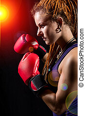 Beautiful girl with red boxing gloves, dreadlocks on a black bac