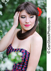 Beautiful girl with red flower on her head in the spring garden