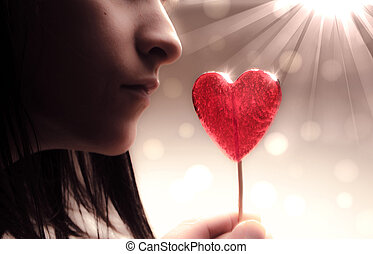 beautiful girl with red heart on bokeh lights background