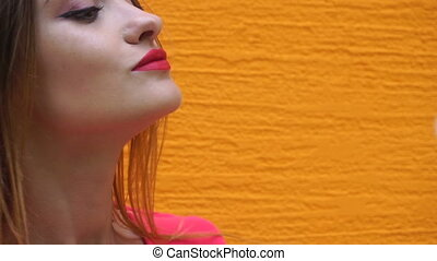 beautiful girl with red lips blowing on a dandelion