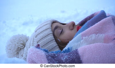 beautiful girl with red lips rests on the snow and smiles
