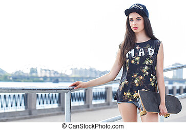 Beautiful girl with skateboard - Attractive woman in a cap