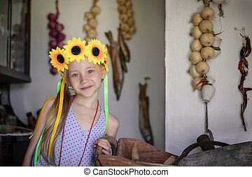 Beautiful girl with sunflowers on the head in a village hut.