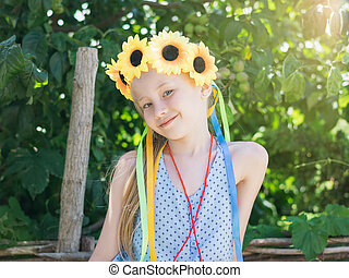 Beautiful girl with sunflowers on the head in the sunshine in front of the tree.