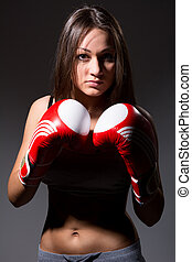 Beautiful girl with the boxing gloves,dark background