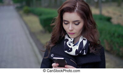 Beautiful girl with the phone on the street