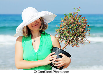 Beautiful girl with tree on the beach