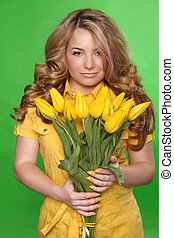 Beautiful Girl With Tulip Flowers over green background. Beauty Model Woman Face.