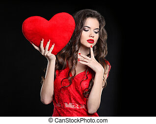 Beautiful girl with valentine heart. Sexy brunette woman posing in red dress isolated on black background. Beauty makeup. Long healthy curly hair.  Manicured nails.