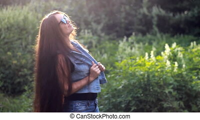 Beautiful girl with very long hair in the sunglasses enjoying a sunny summer afternoon at sunset.