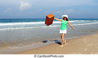 Beautiful girl with vintage suitcase on the beach
