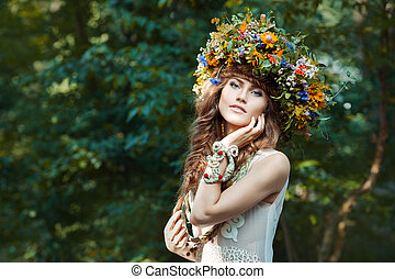Beautiful girl with wreath on the head of  field flowers.