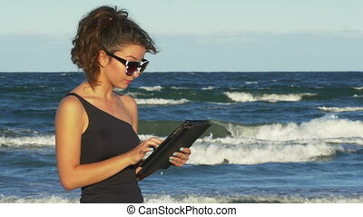 Beautiful girl working on her tablet pc by the sea